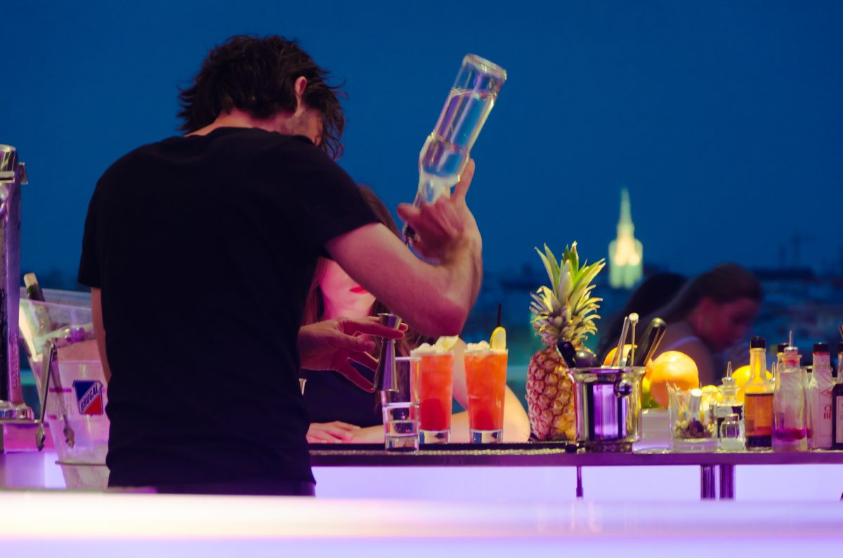A guest making himself a drink at a Cancun party.