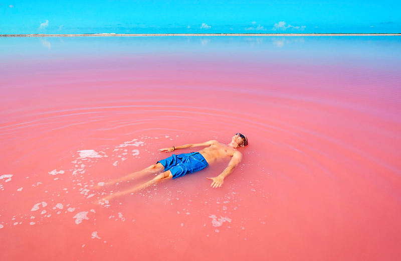 A man soaking in the Pink Lake of Las Coloradas in Mexico