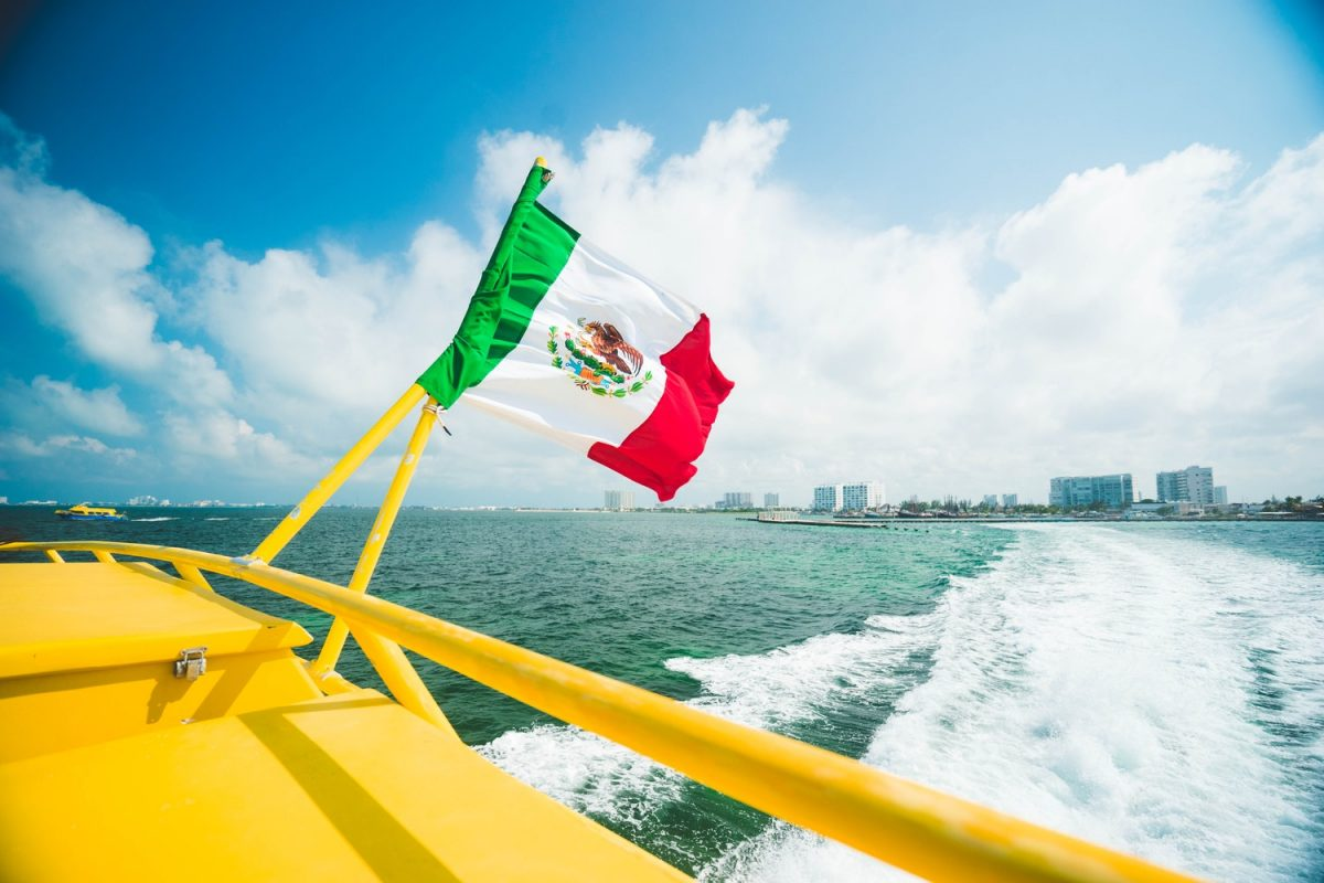 Mexico's flag waving over Cancun's sea