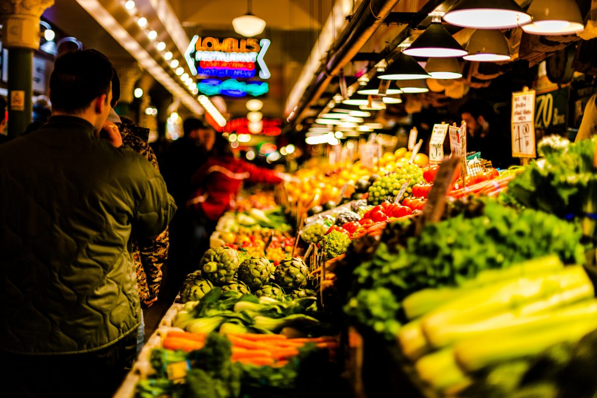 Crowded covered marketplace with many fresh fruits on display