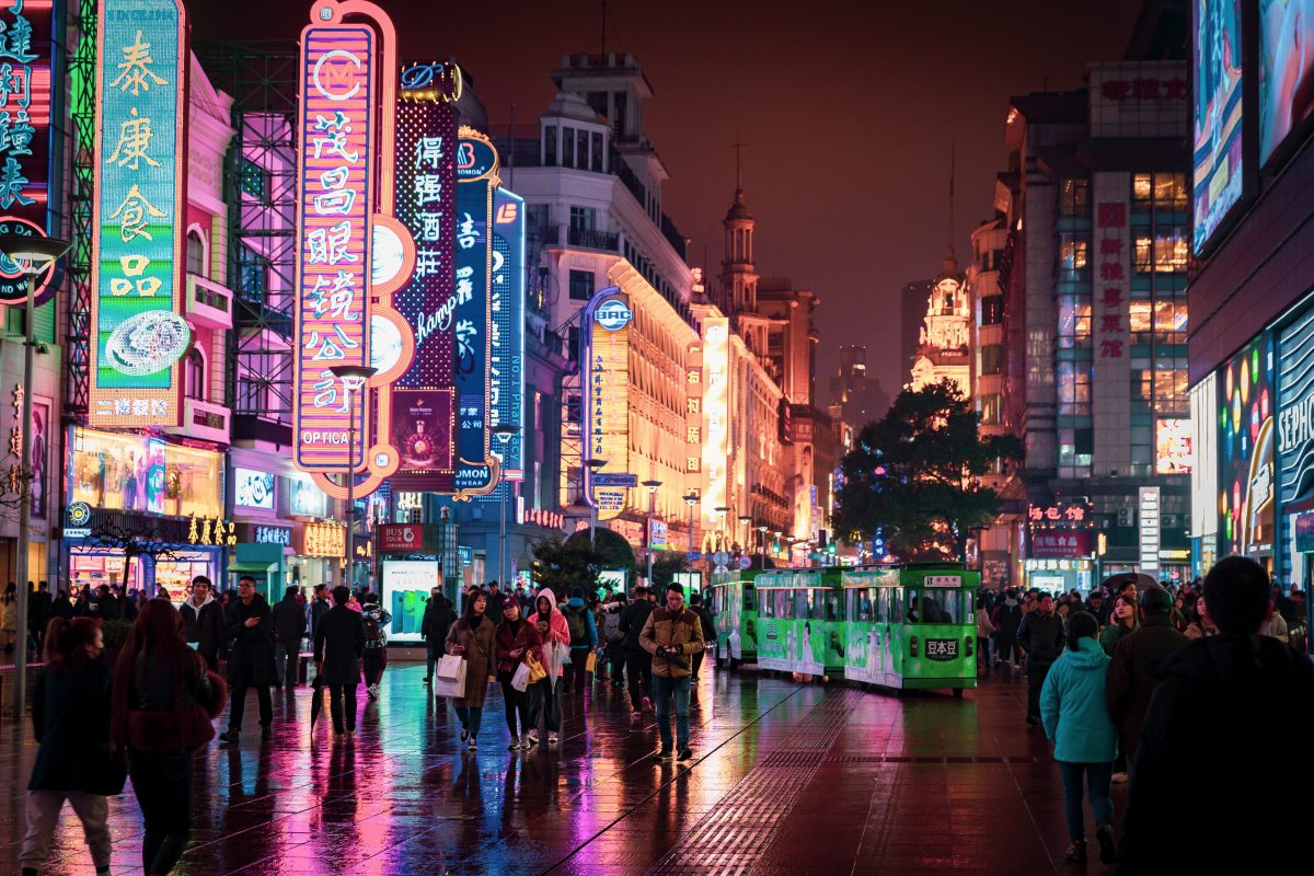 Shopping crowd at Nanjing Road, Shanghai's premier pedestrian retail arcade. There are bright neon lights attached to the buildings