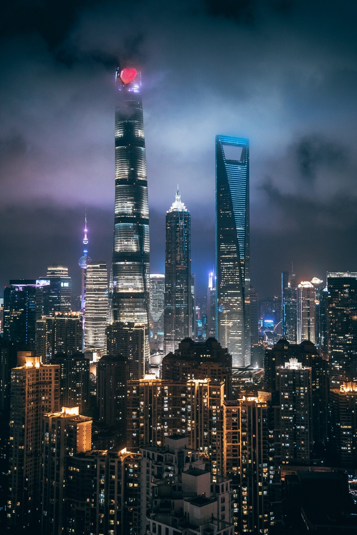 The world's first skyscraper trio towering over other buildings in Shanghai with the night skyline in the background