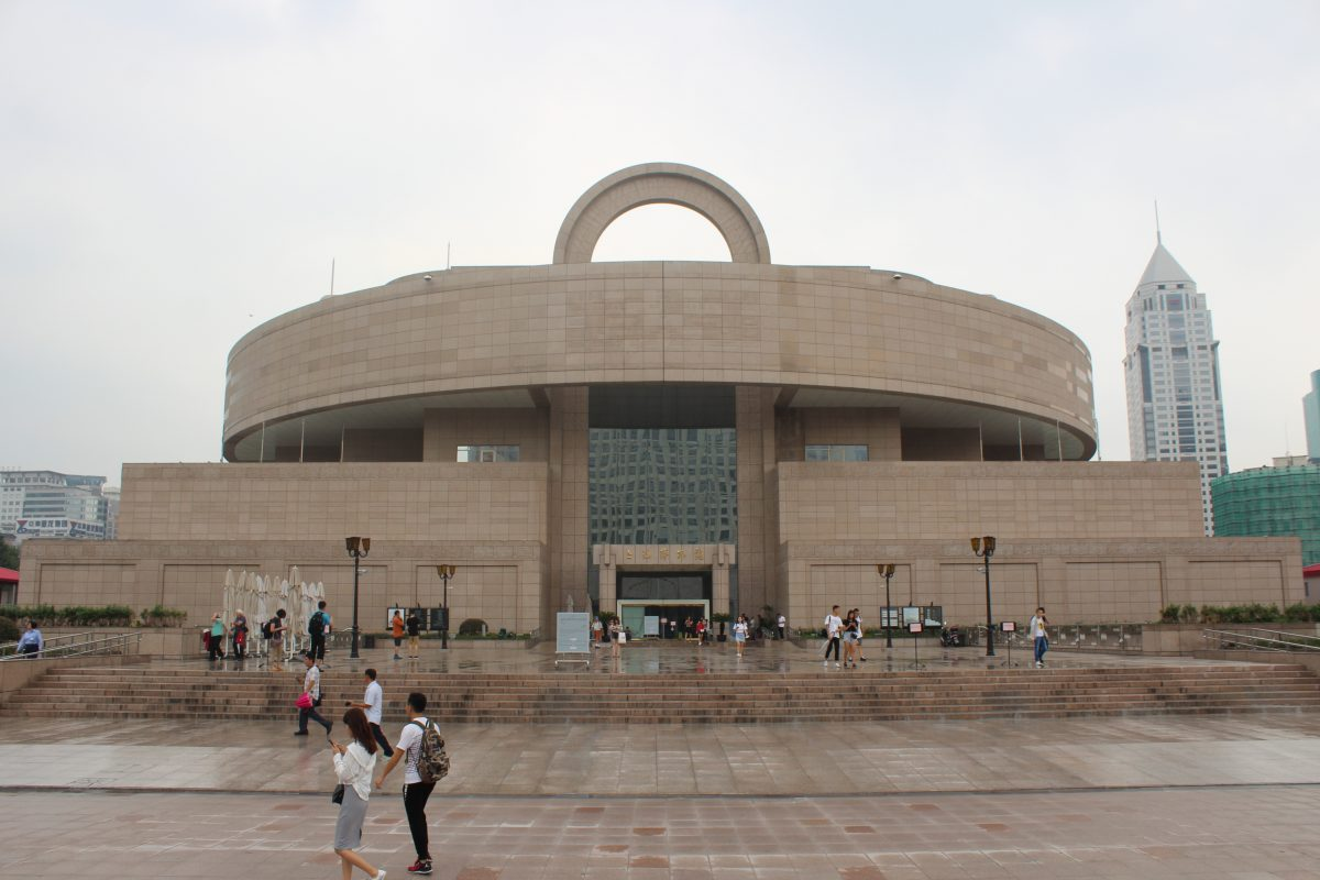 Main entrance of Shanghai Museum on a rainy day as locals are going about their daily routine