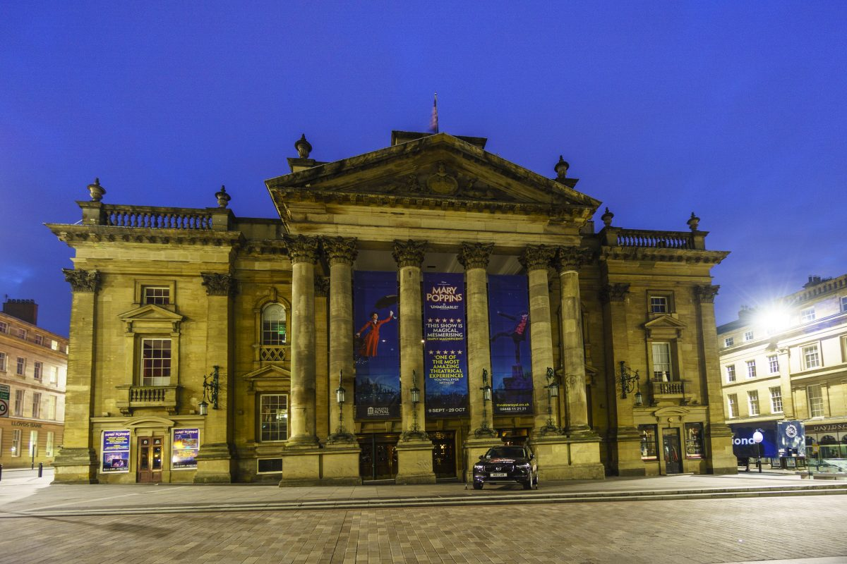 Evening view of the Theatre Royal with banners depicting upcoming events
