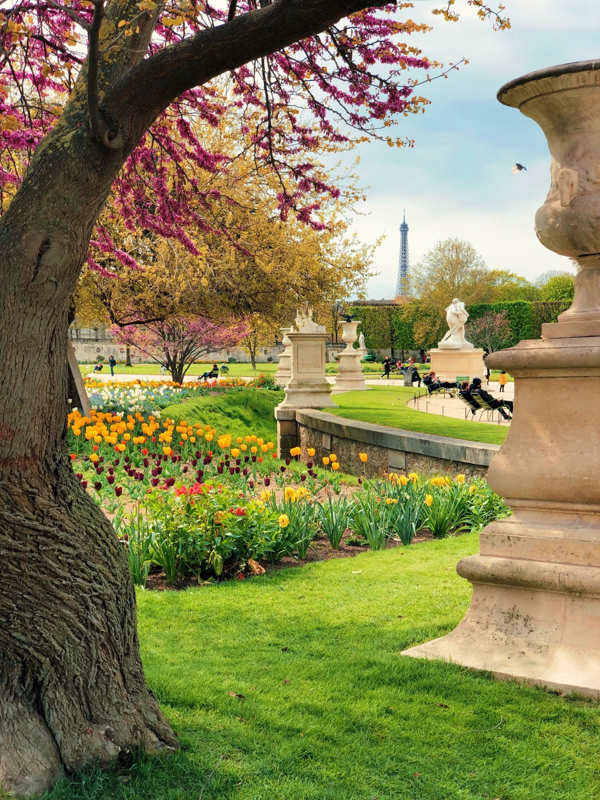 A beautiful day at the park with a sculpture and flowers in view