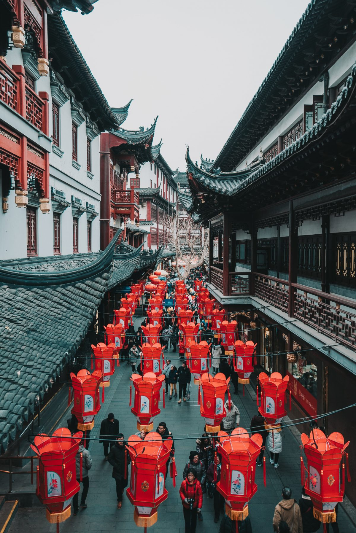 Bright red lanterns that adorn the streets of Yu Garden as pedestrians walk by admiring the classic oriental architecture