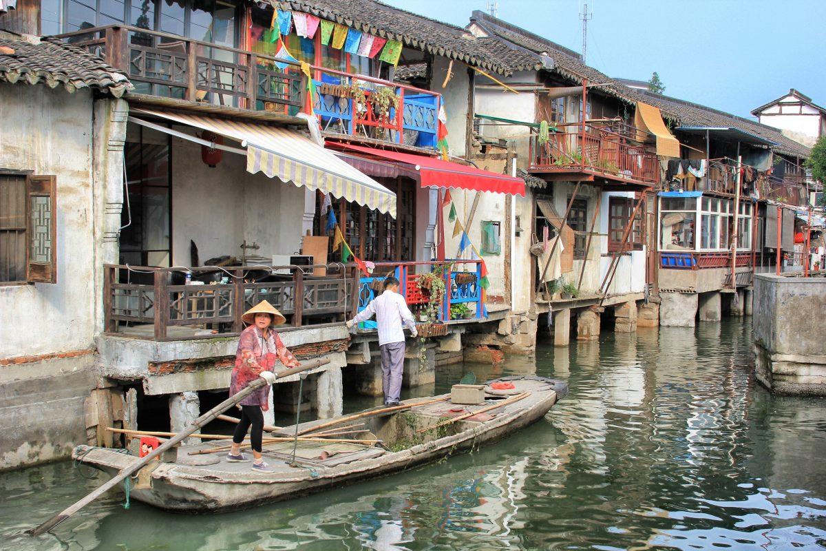 An elderly couple navigating a wooden boat through a stream at Zhujiajiao Water Town