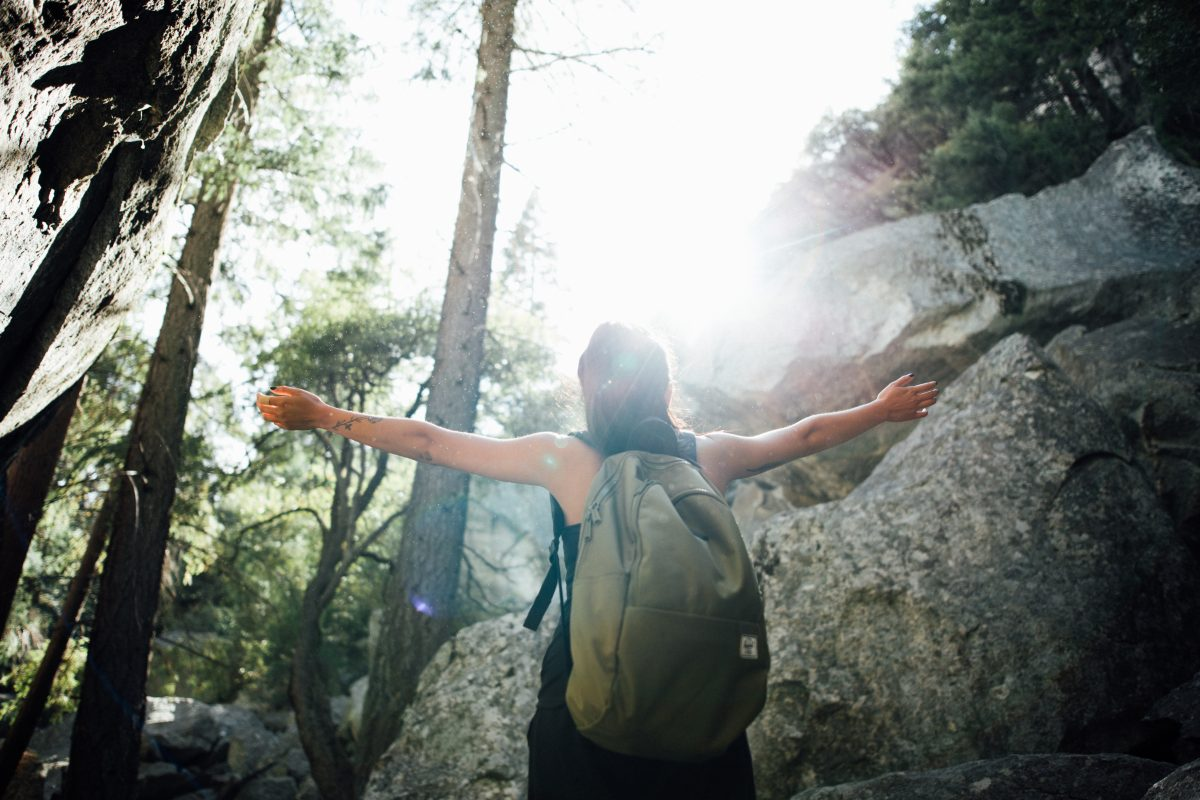 Woman with a backpack raising her arms in the forest