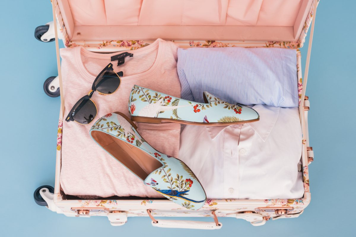 Colorful clothes and shoes in a travel bag