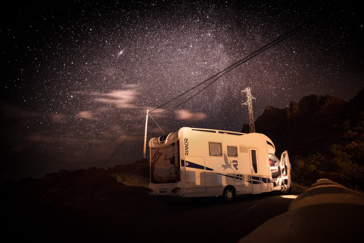 An RV motorhome parked under the stars