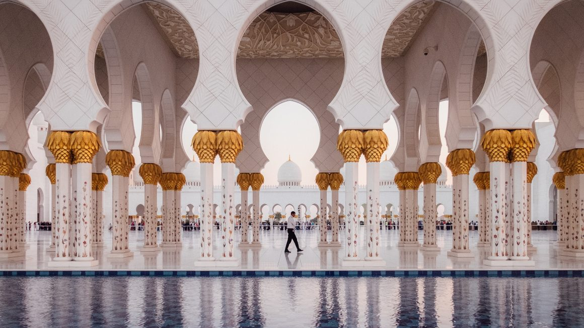 White golden mosque reflection on pool Abu Dhabi