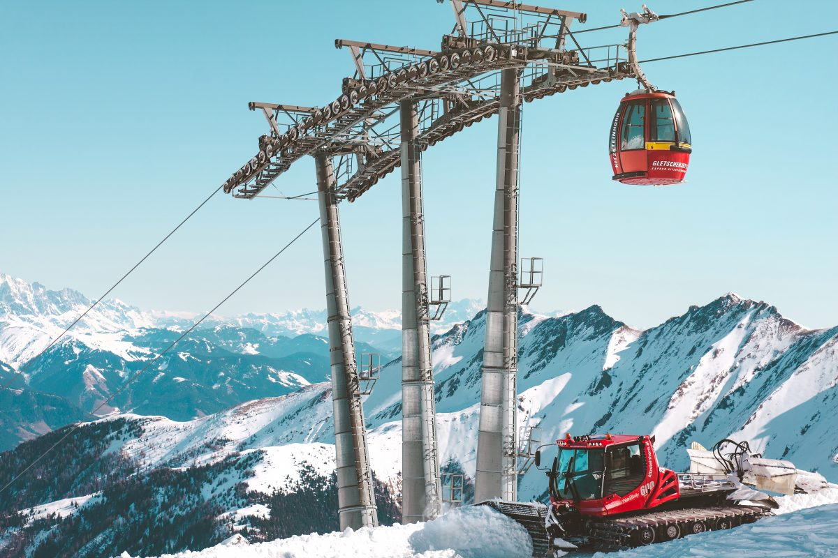 Red cable car and snowy mountains