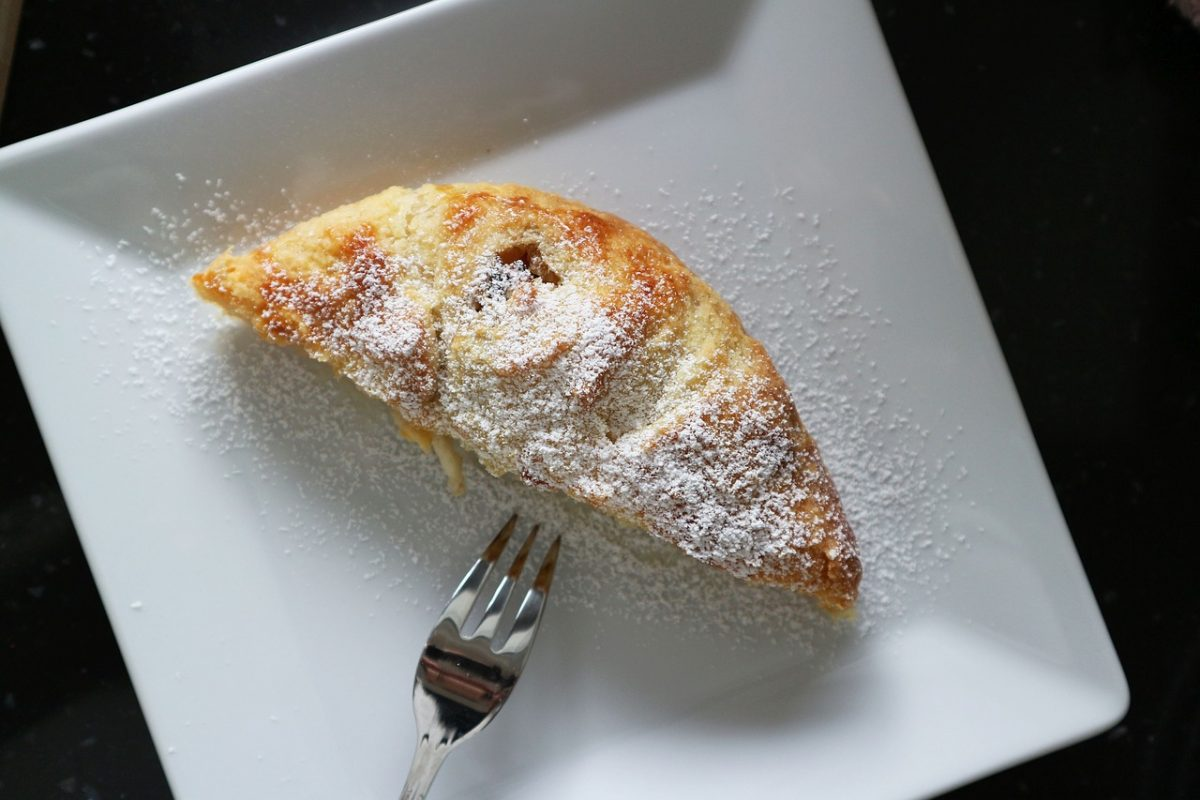 Apple strudel on a white plate with fork on the side