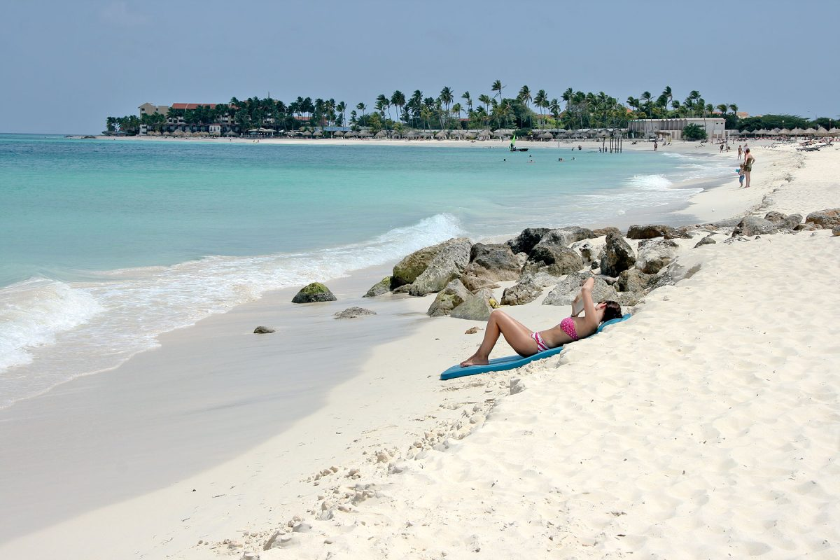 Woman relaxing on Eagle Beach in Aruba