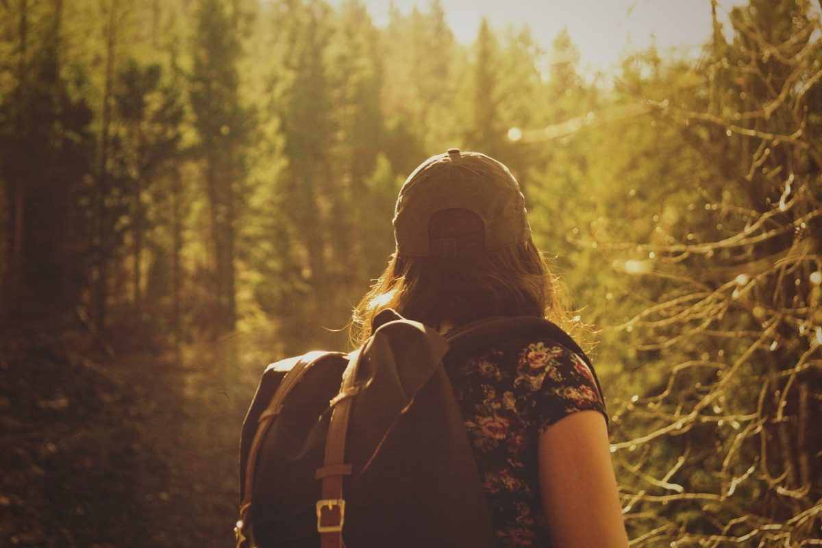 Woman with her backpack hiking in the woods