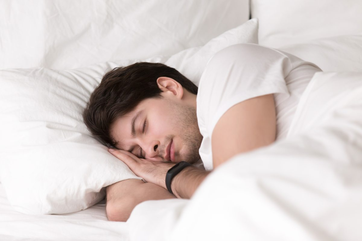 Man is asleep in cozy white bed at night