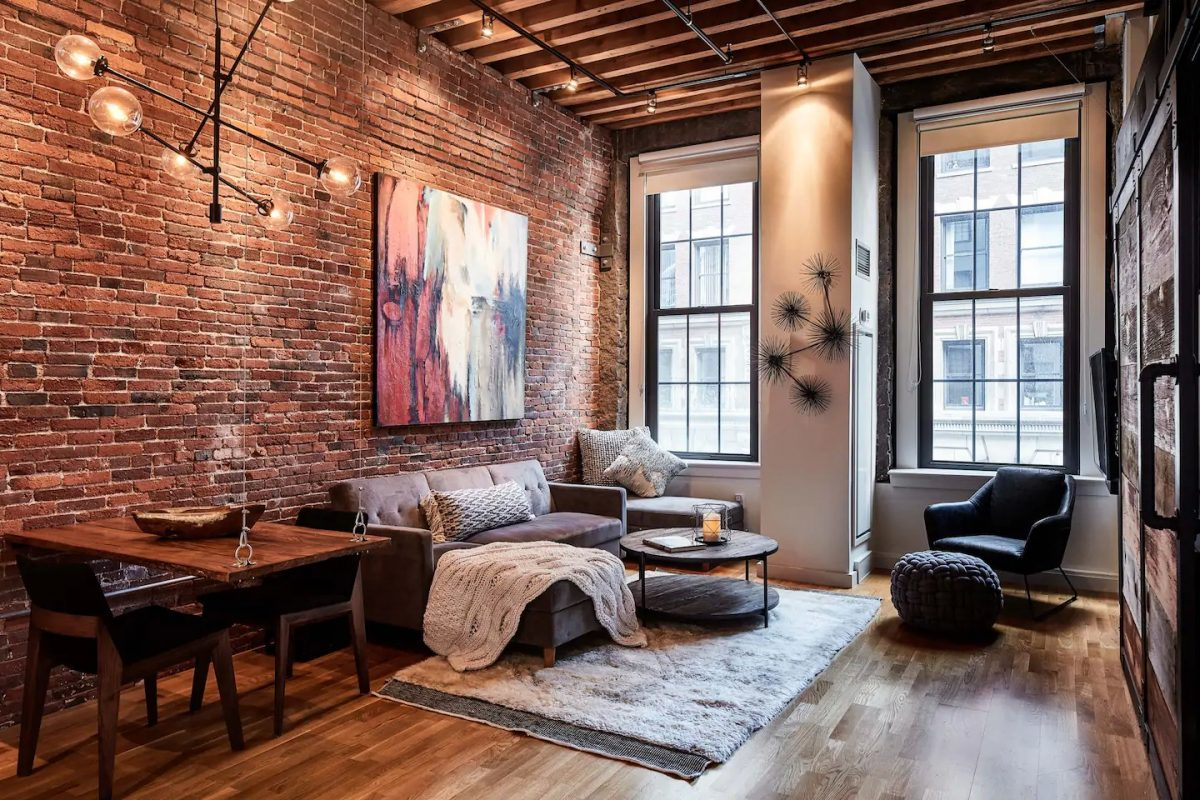 This unique Airbnb Boston loft with soaring ceilings and a brick wall retains its original warehouse charm