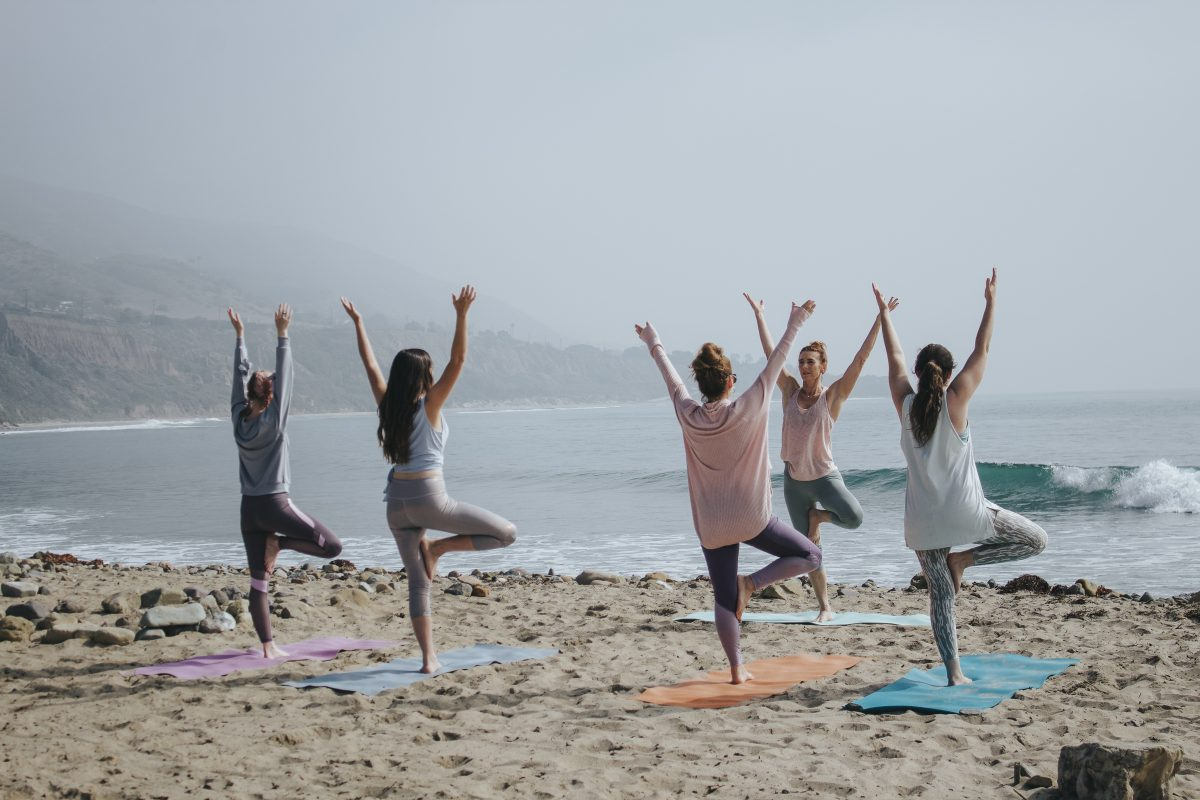 group of women practicing yoga on a beach