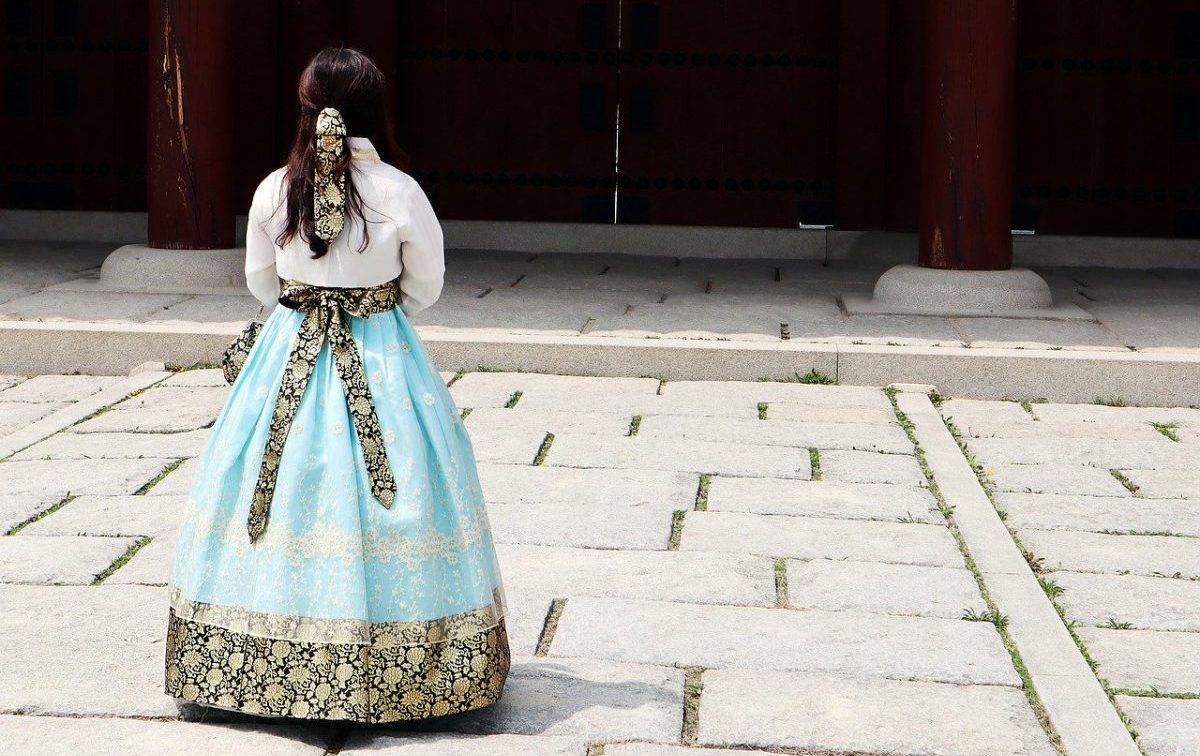 A lady wearing a moden Korean Hanbok in turquoise blue