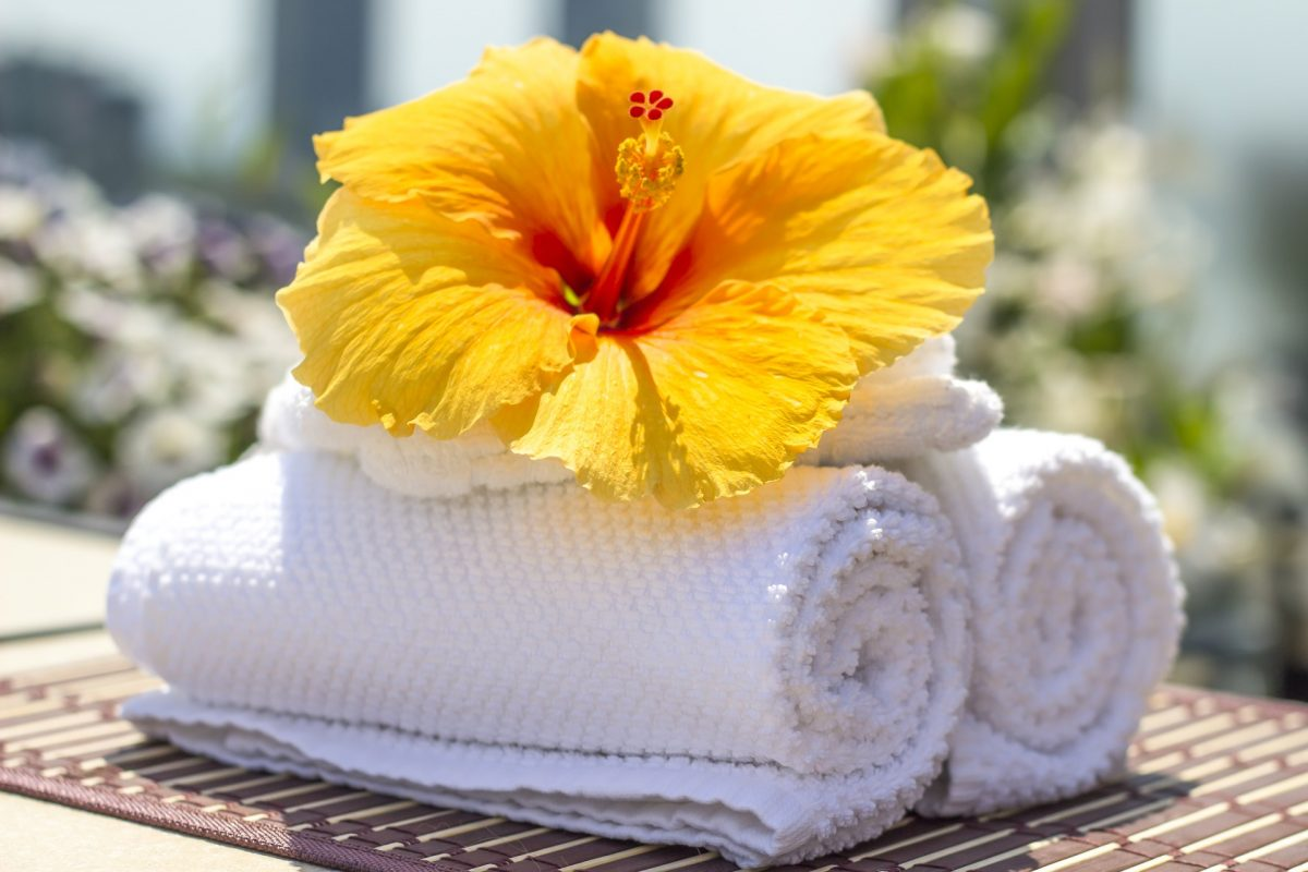 stack of white towels with a yellow flower on top
