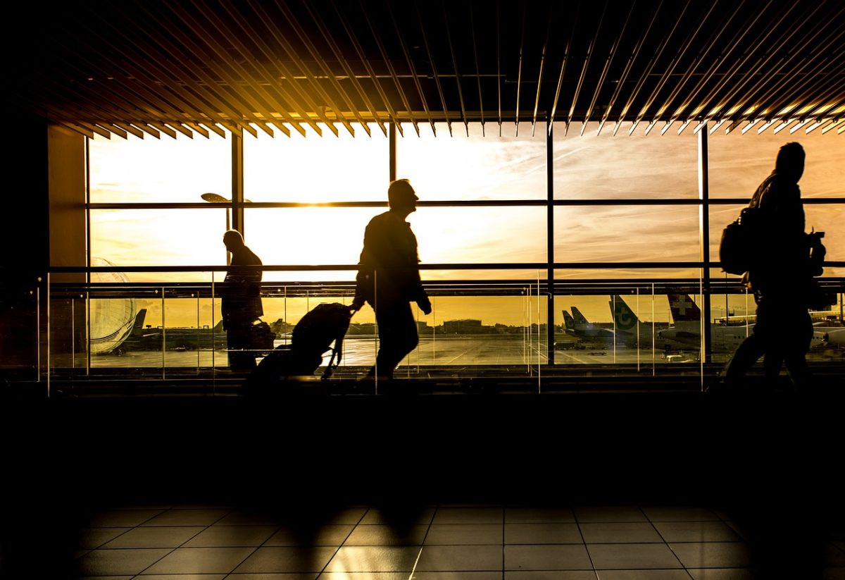 People walking through an airport at sunset