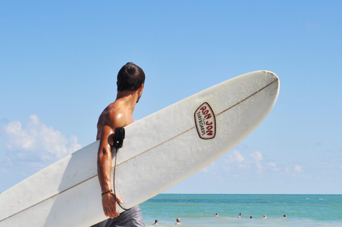 Man holding surf board in beach