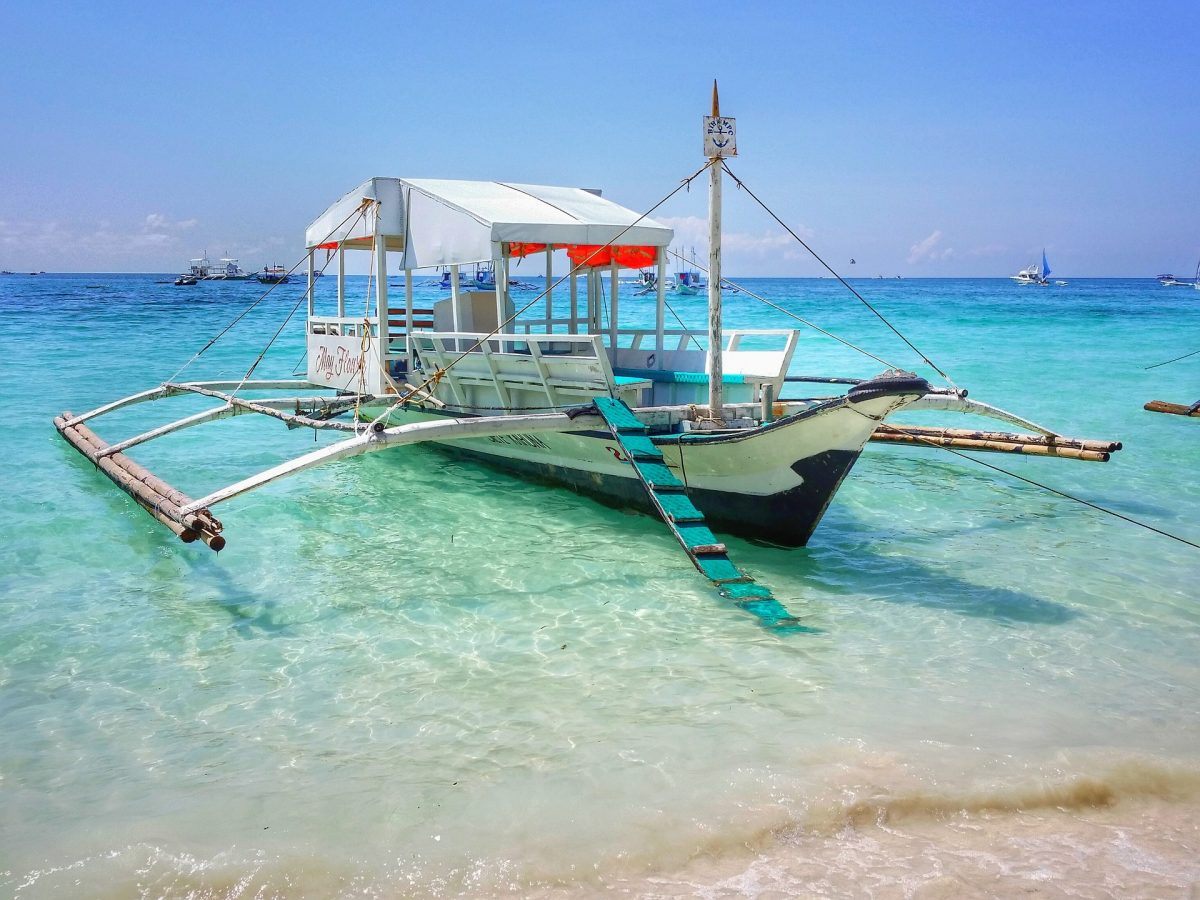 A boat docks on a beach in Boracay, Philippines