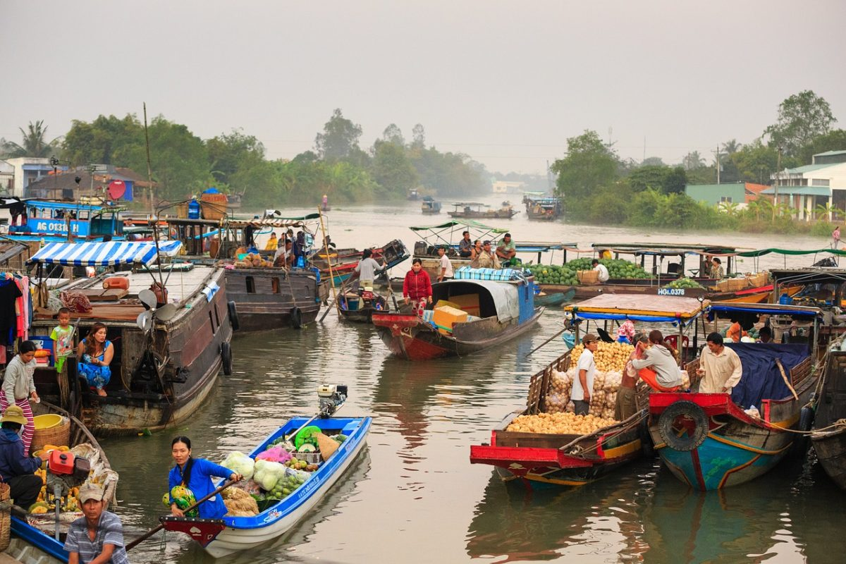River in Thailand full of floating market boats and stilt houses