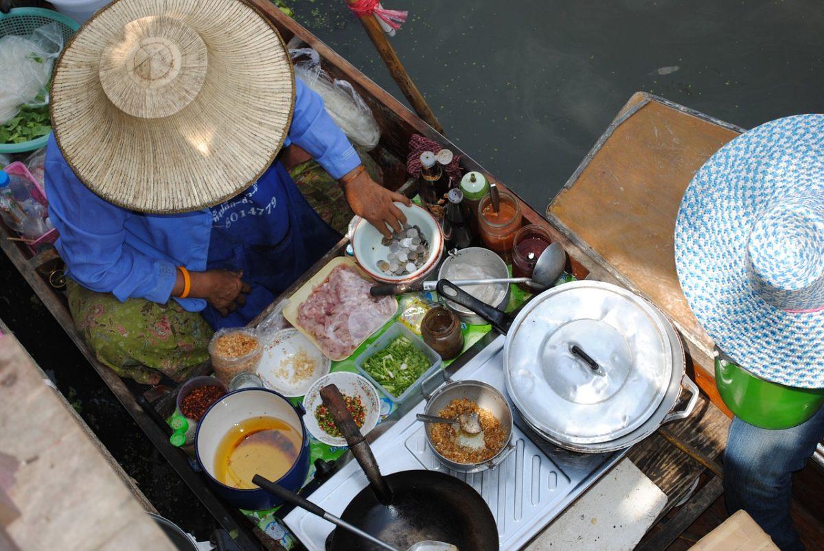Food merchant preparing hot food on a floating boat