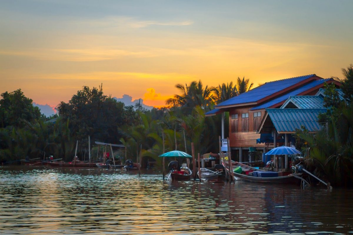 Stilt houses and floating market boats on a river at sunset