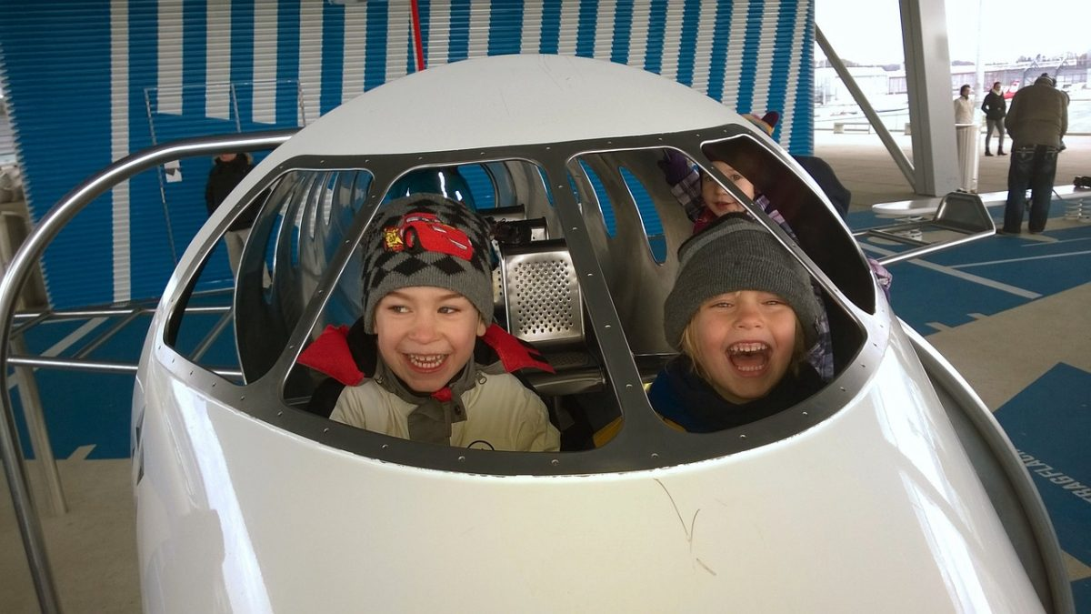 Kids sitting in a cockpit at Dulles Airport