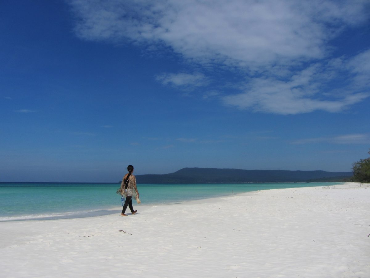 A woman walks on the beach in Koh Rong Island, Cambodia