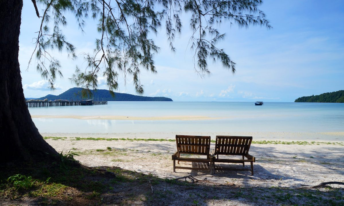 Two outdoor chairs under a tree on a beach in Koh Rong Sanloem, Cambodia