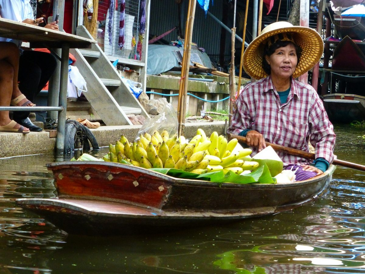 Lady in a floating boat selling bananas