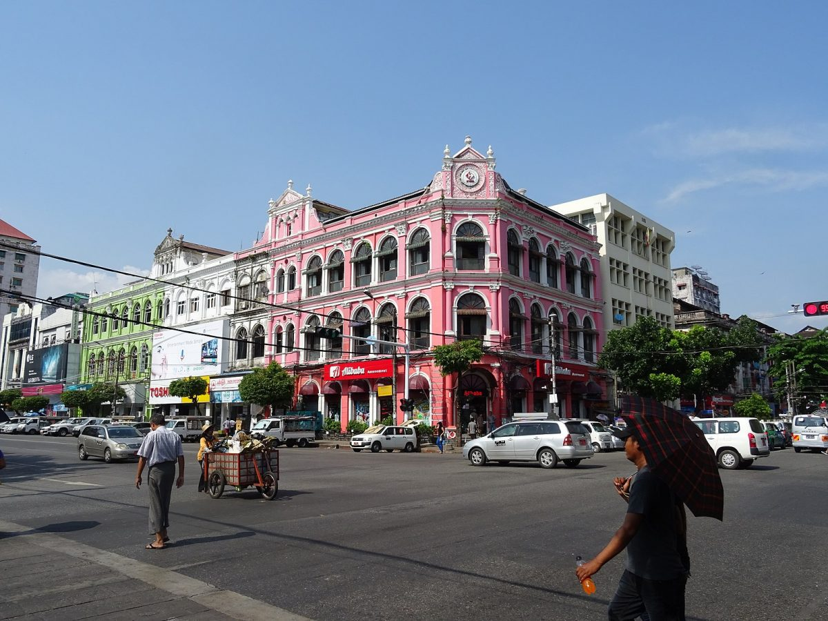 driving cars and people walking at the busy Pansodan Street in Yangon
