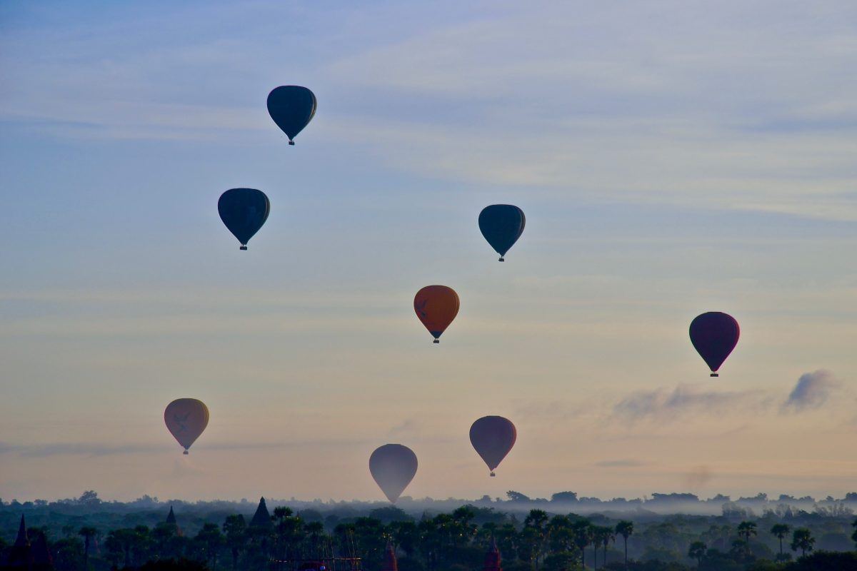 hot air balloons fly in the skies of Bagan