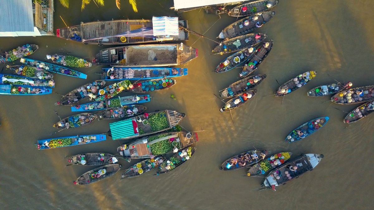 Cinematic shot of local vendors in the floating market on a scenic evening of Can Tho