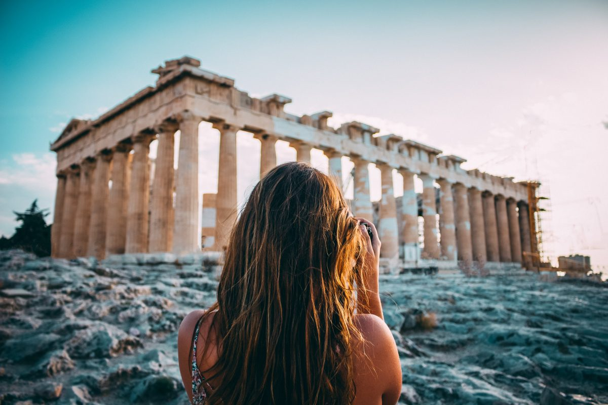 a woman taking a photo of the Parthenon in Athens