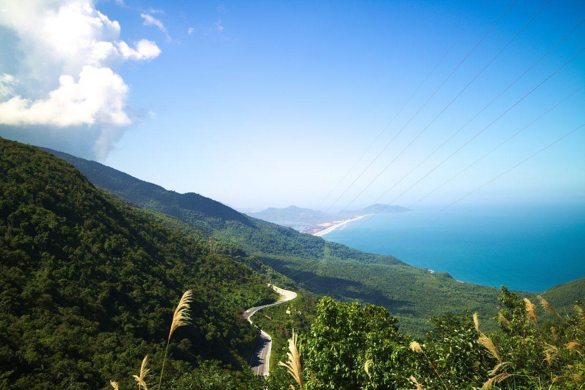 A long winding road (Hai Van Pass) runs up a mountain