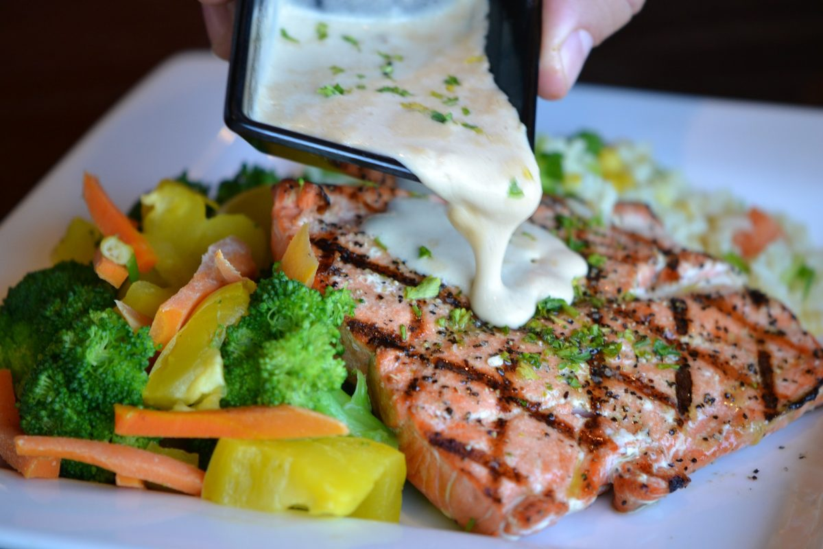 cream sauce drizzled over grilled salmon with vegetables on the side