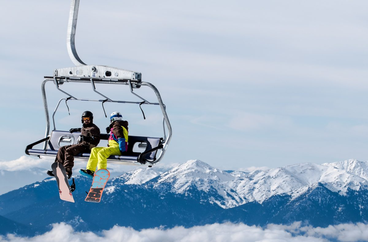 two skiers sit on a cable car overlooking the snowy mountains