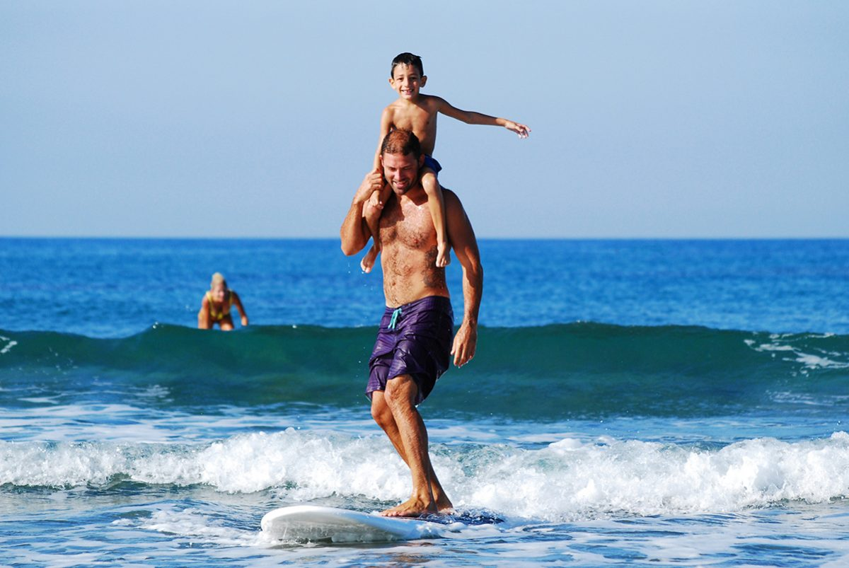 a man with a child sitting on his shoulders surfing