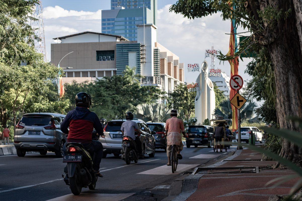 laid back city vibe while old man cycling in Surabaya city