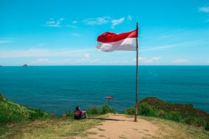 an indonesian flag on a cliff overlooking the beach