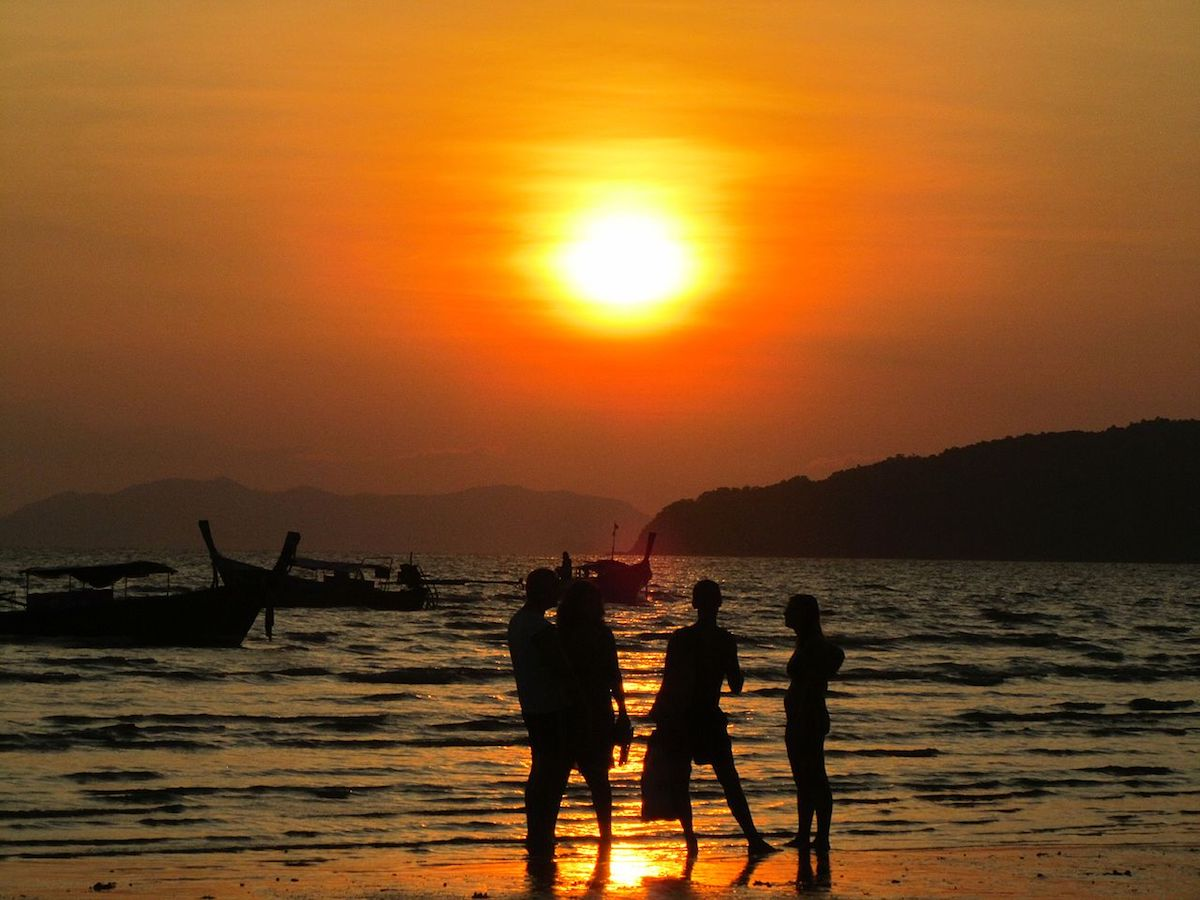 four people enjoying the view of the sunset on the beach shore