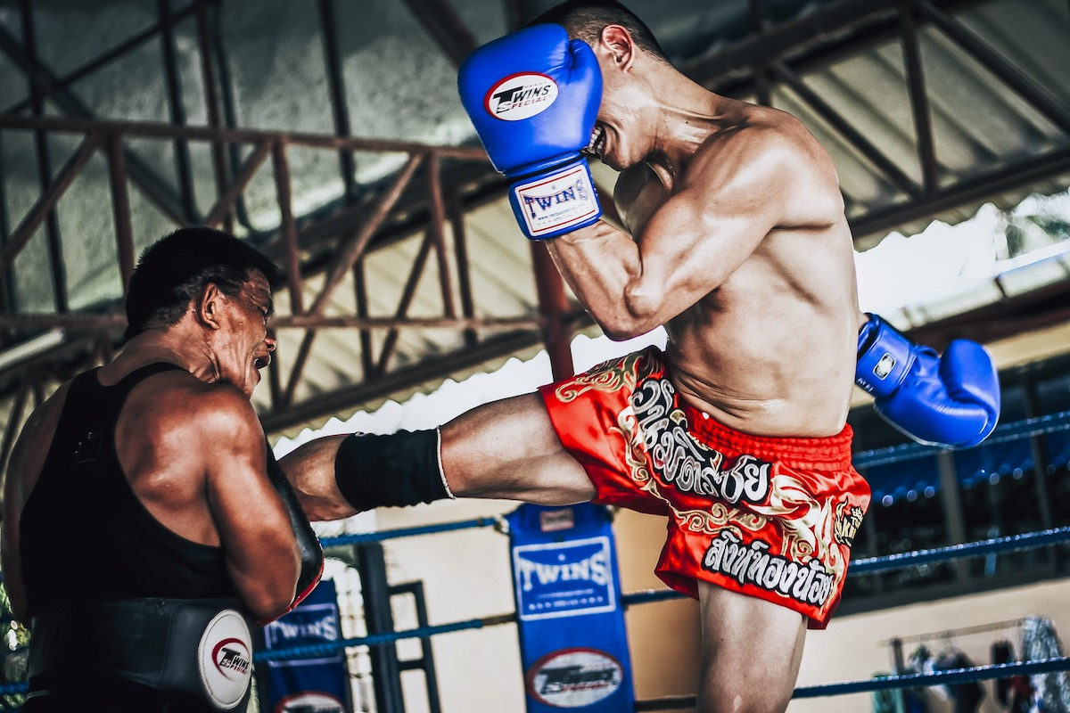 two people having a muay thai fight in the ring