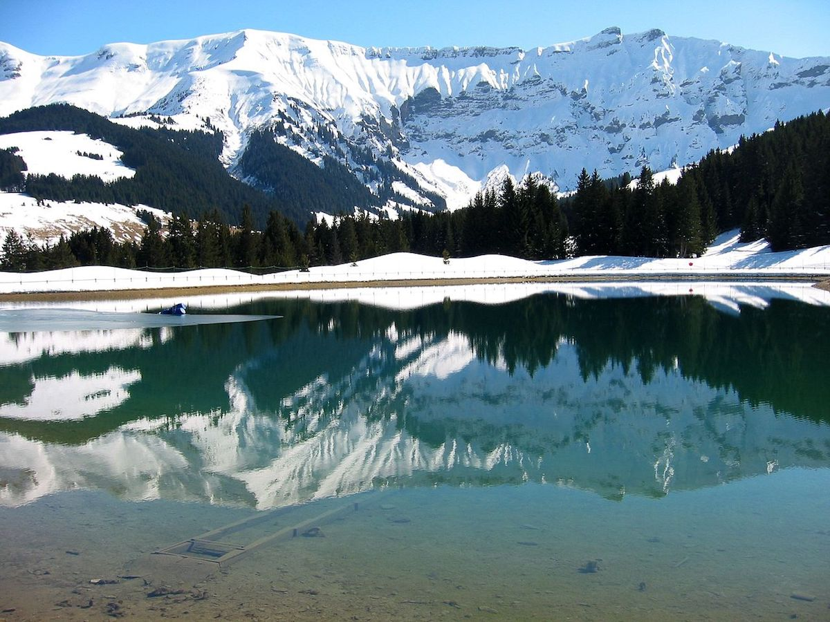 Turquoise water of the Megeve lake surrounded by the snow-capped French Alps