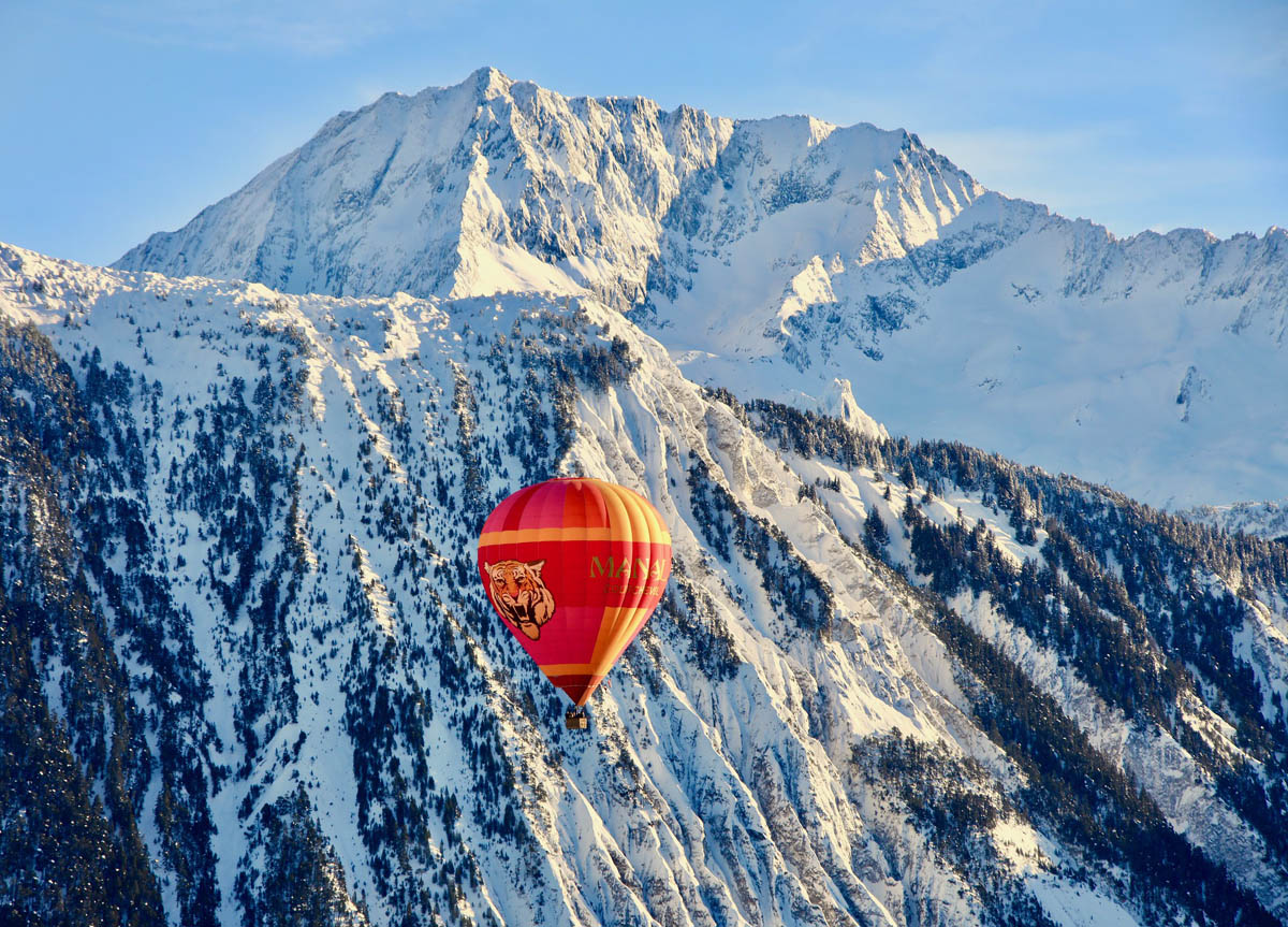 a hot air balloon flying across the French Alps