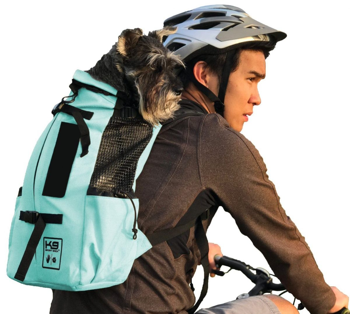 Photo of the K9 Sport Sack AIR in mint green carrying a black Terrier on a cyclist's back who is wearing a grey helmet, a brown long-sleeved top, and grey shorts on a bicycle