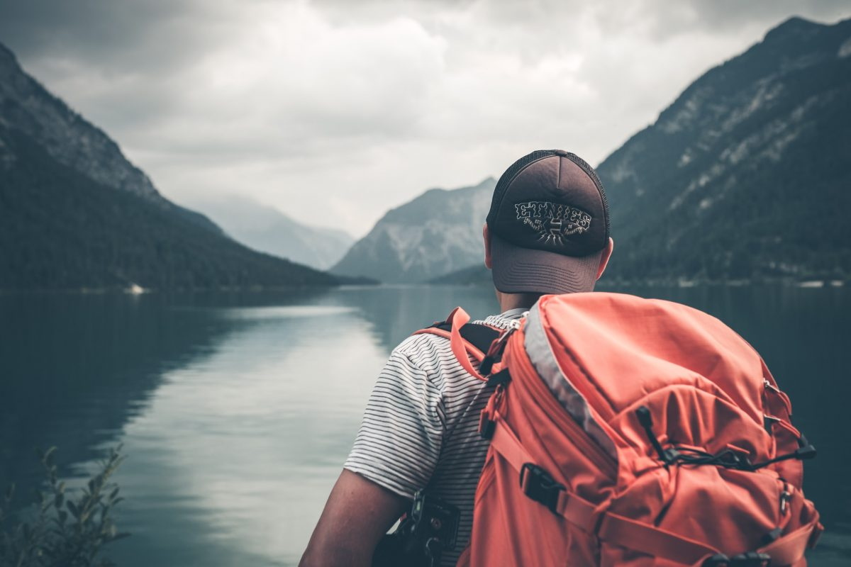 A lonely backpacker with a red backpack